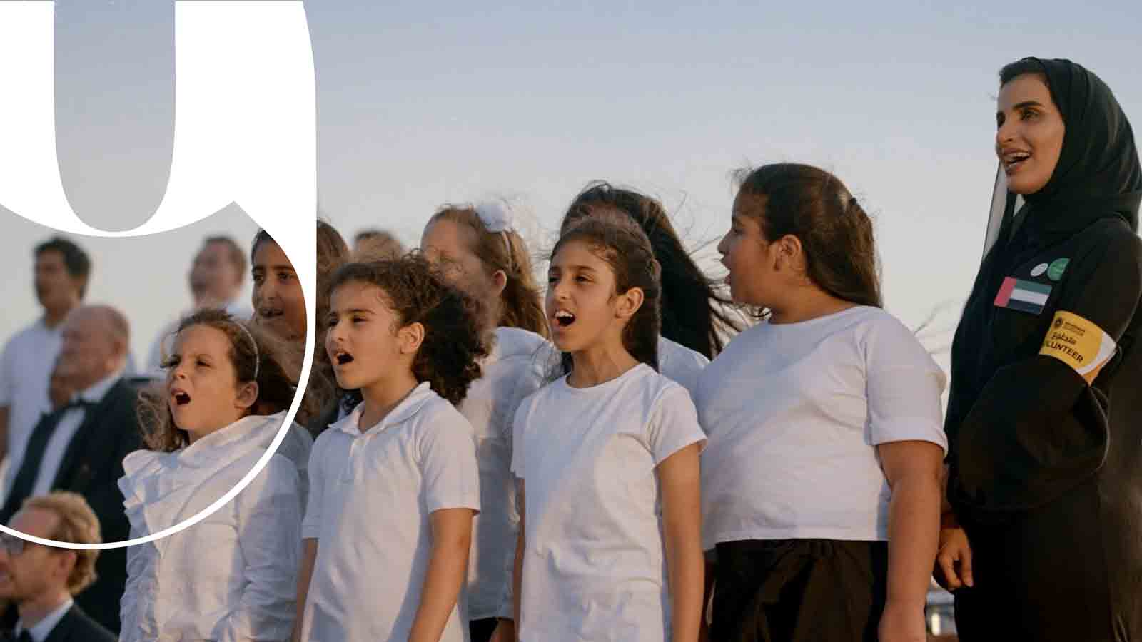 A group of children happily singing as part of a concert in the desert