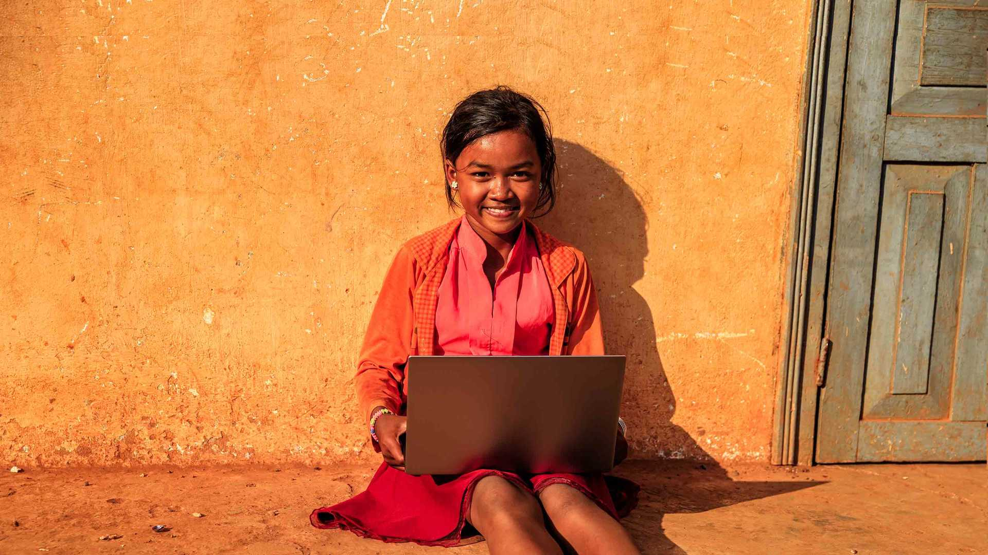 Expo Live - Cambodian girl sitting against a wall using a laptop