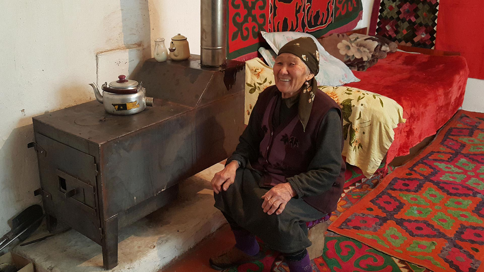Old Kyrgyz woman sitting down smiling