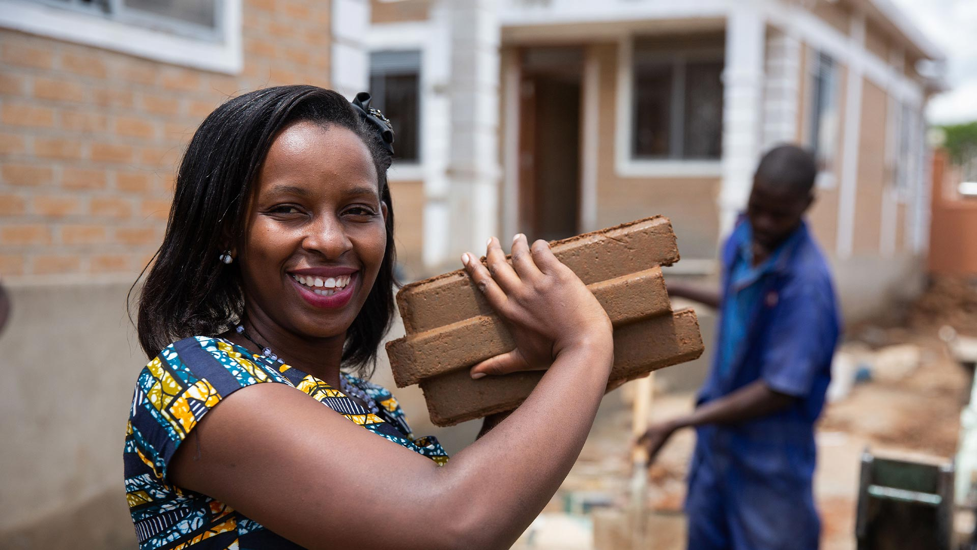 Woman carrying a brick smiling