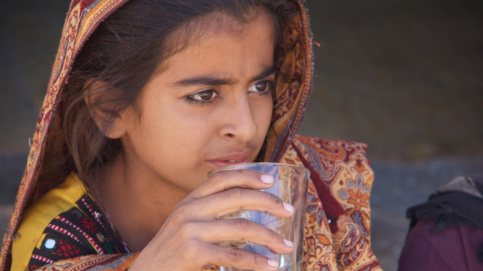 A Pakistani girl holding a glass of water