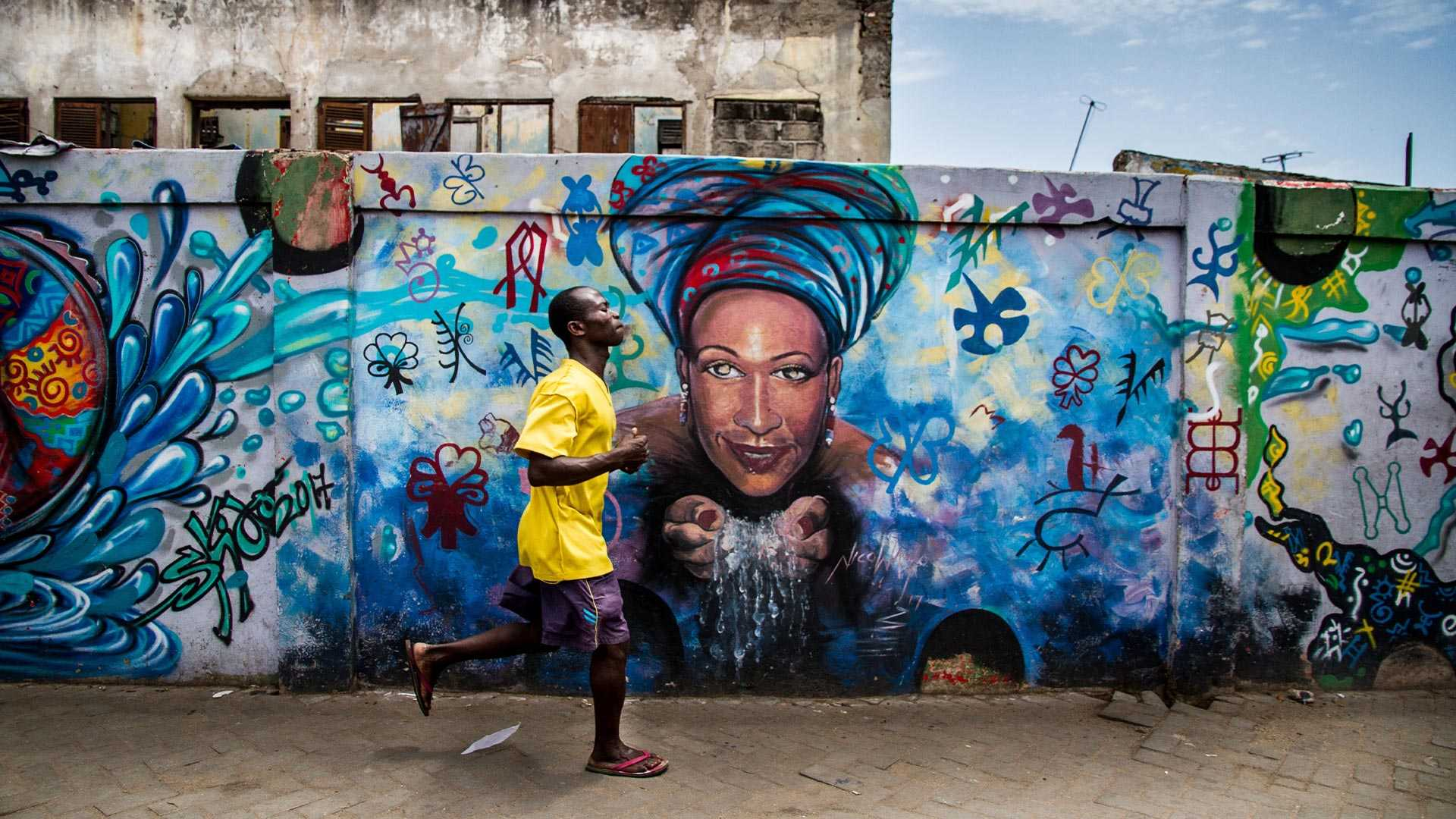 A man in Ghana running in the street in front of a wall painted with urban art